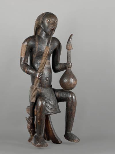 Diese Figur stellt einen König aus Bakowen im Kameruner Grasland dar, der die Symbole seines hohen Statuts trägt: geschliffene Zähne, Palmweinkalebasse mit Trinkhorn und Prunkpfeife. Er sitzt auf einem Hocker, was ebenfalls ein Zeichen seiner Würde ist.