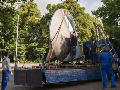 Vier Männer sichern auf einer LKW-Ladefläche eine runde, ca. 3,5 Meter hohe Stahlskulptur.