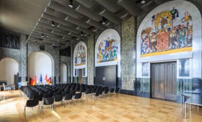 Bestuhlter Saal mit Mosaiken an den Wänden