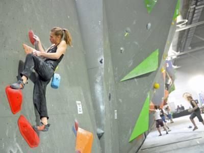 Foto: Eine junge Frau beim Bouldern an der Kletterwand.