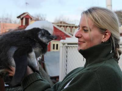 Frau hält Pinguin auf dem Arm