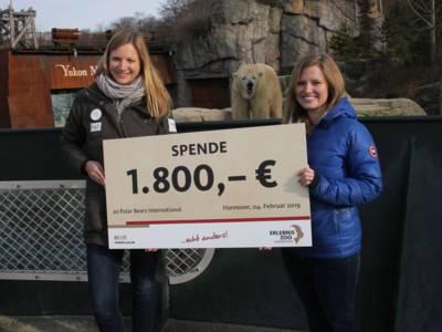"""Zwei Frauen halten einen großen Scheck mit Aufschrift """"1800 Euro"""" hoch"""