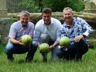Drei Männer halten jeweils eine beschriftete Melone in der Hand