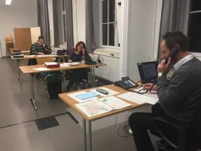 Zwei Männer und eine Frau in einer Telefonzentrale.