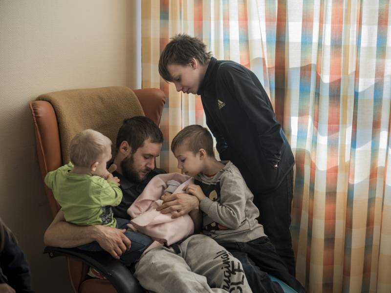 Mann im Sessel hält einen Säugling im Arm, um ihn herum stehen zwei kleine Jungs und eine Frau.