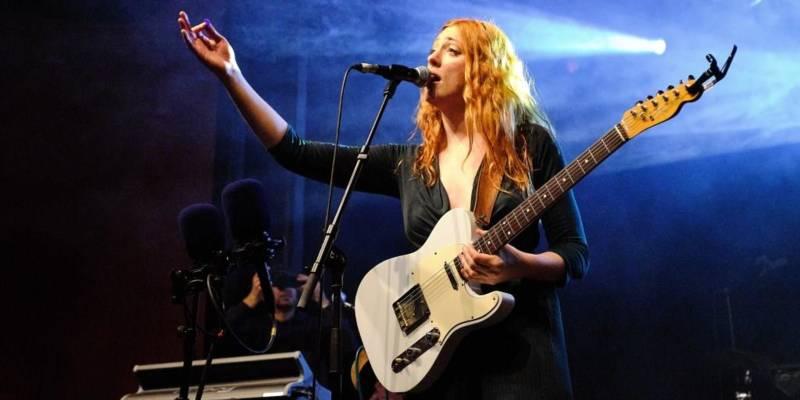 Eine Frau steht auf einer Bühne und singt in ein Mikrofon, um sie herum strahlt blaues Licht. Ihre rechte Hand ist zu einer einladenden Geste weit ausgestreckt, ihre linke Hand hält eine E-Gitarre.