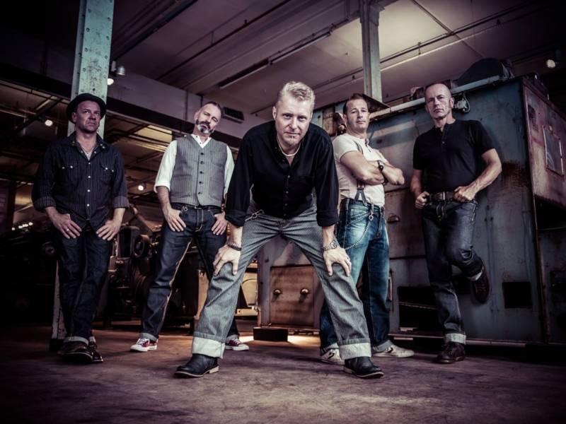 Fünf Männer stehen in einem industriellen Setting.