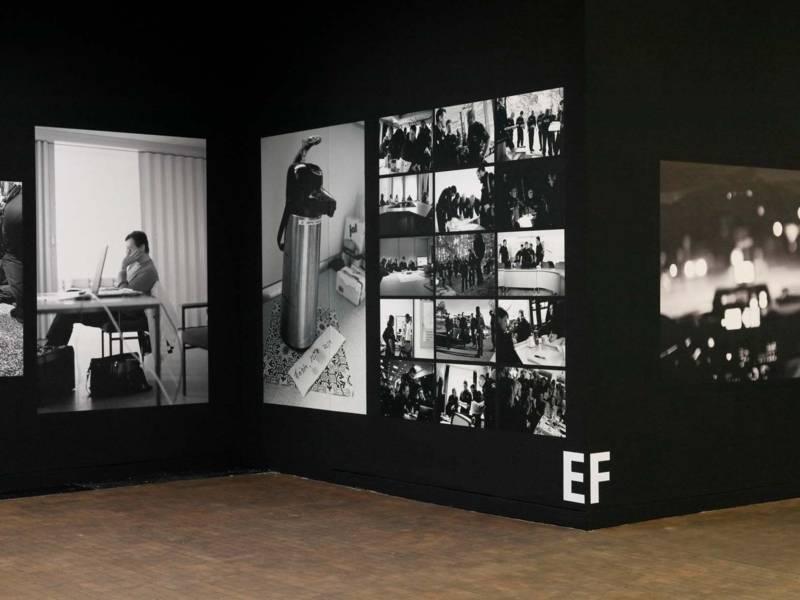 Blick in eine Ausstellung, die große Fotografien in schwarz-weiß zeigt. Sie hängen an einer schwarzen Wand.