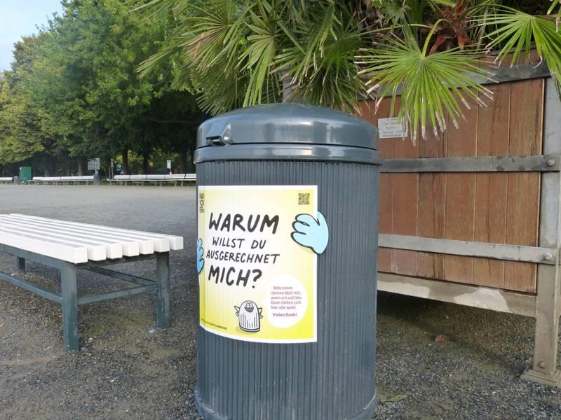 """Mülleimer neben einer Bank. Darauf steht """"Warum willst Du ausgerechnet mich?""""."""