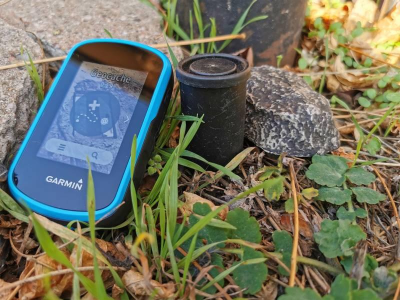 Blaues Geocachegerät und eine Fotodose zwischen Steinen und Gras.