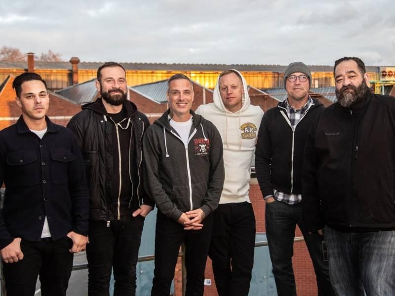 Sechs Männer stehen auf einem Flachdach. Im Hintergrund sind die Dächer von Industriegebäuden zu sehen. Alle schauen lächelnd in die Kamera.