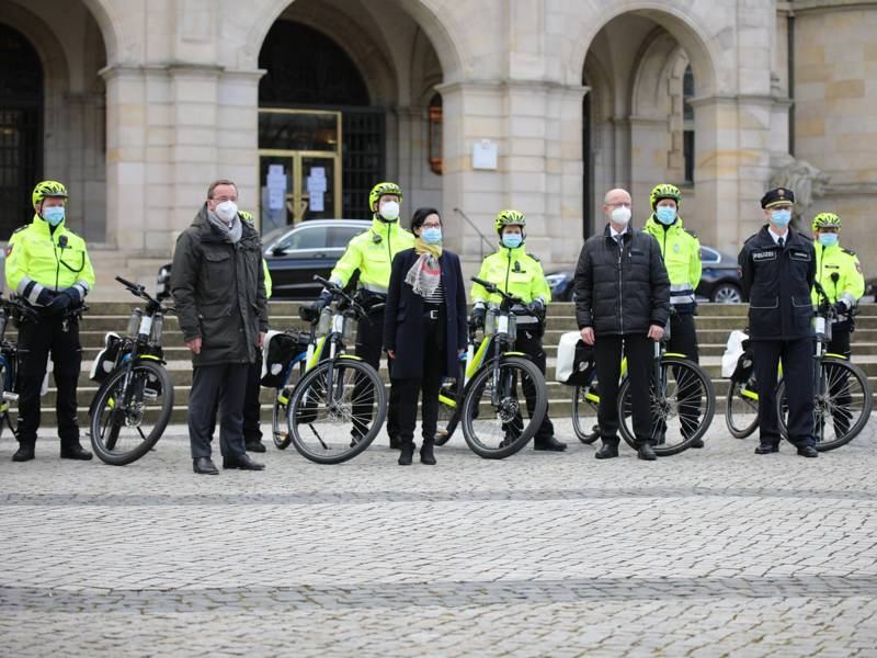 Zehn Personen, darunter einige mit Fahrrad, mit Maske und Abstand vor dem Neuen Rathaus