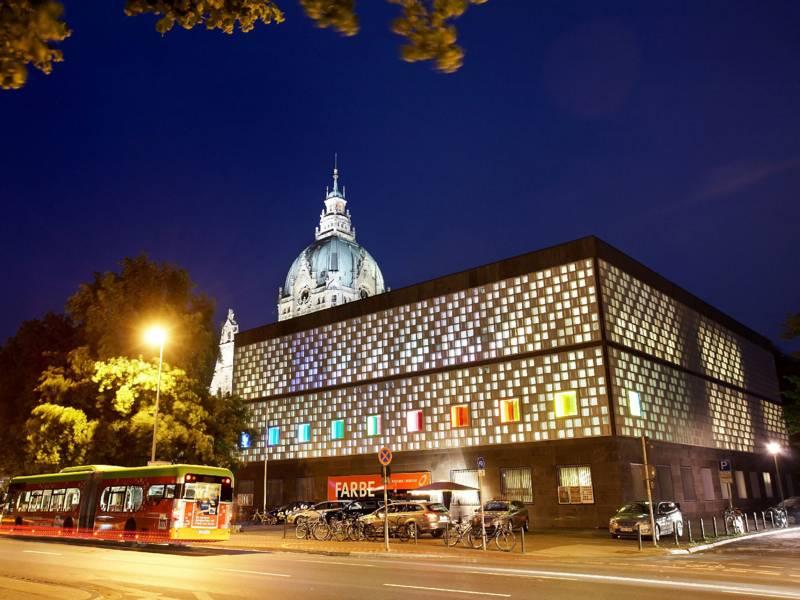 Ein Museum von außen im Abendhimmel. Im Hintergrund das Neue Rathaus.