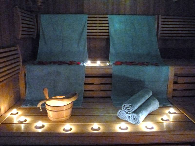 Sauna mit Handtüchern, Kerzen und Saunaeimer