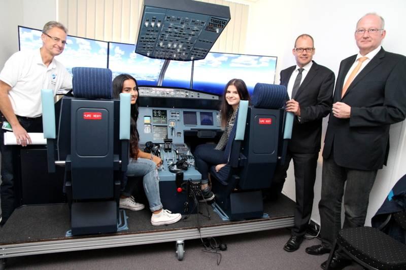 Präsentieren das Projekt im Airbus A320-Flugsimulator: Martin Dutschek (v. l.) vom Unternehmen Sim&Learn, die beiden Schülerinnen Rinna Kuraischi (16) und Regina Ruff (15) mit Ulf-Birger Franz, Wirtschaftsdezernent der Region Hannover, und Hans-Ulrich Koch, Teamleiter in der Berufsberatung der Agentur für Arbeit.