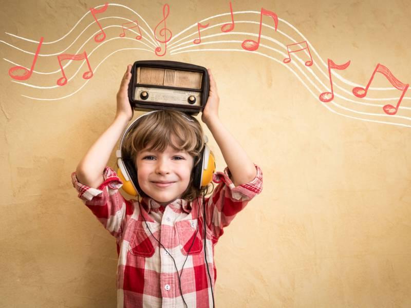 Ein kleiner Junge im rotweiß-karierten Hemd hält ein kleines Retroradio über seinem Kopf. Er trägt außerdem Kopfhörer und es sind gezeichnete Notenlinien und Noten zu sehen.