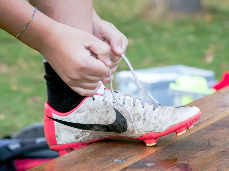 Zwe Hände binden die Schnürsenkel eines Fußballschuhs