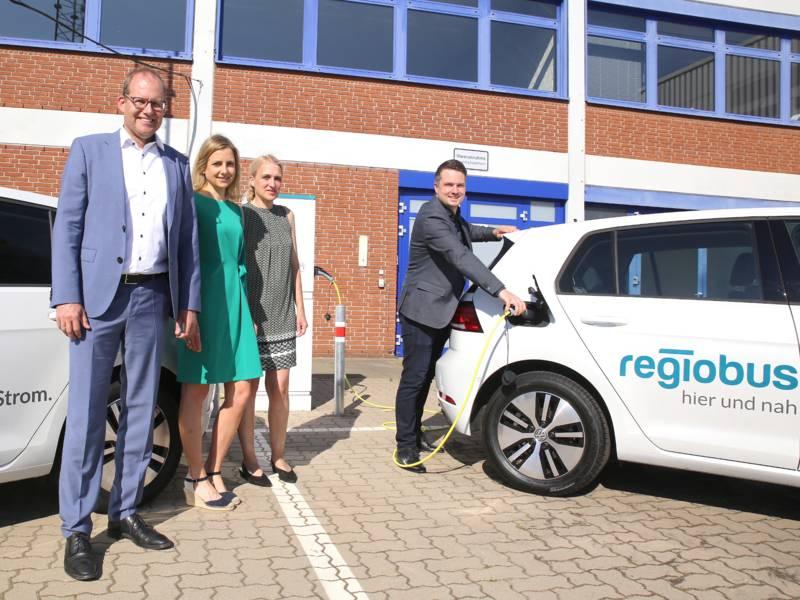 Vier Personen stehen zwischen zwei Elektroautos. Eines der Fahrzeuge wird betankt.