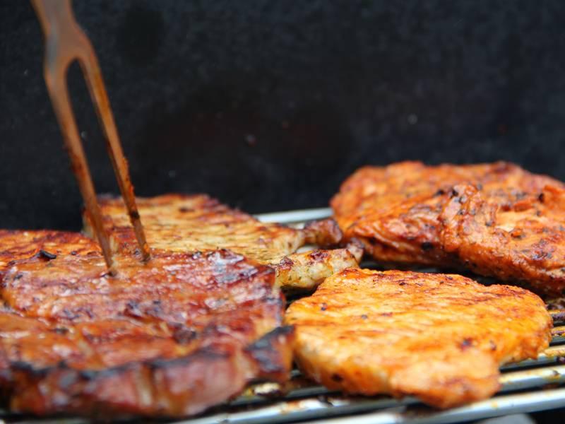 Vier Scheiben Fleisch auf einem Grillrost. In eine der Scheiben steckt eine Grillgabel, zum Wenden oder Runternehmen.