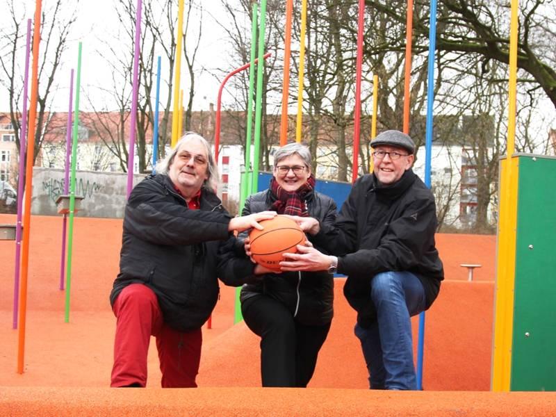 Eine Frau und zwei Männer stehen auf einem Fitness-Areal und halten einen Basketball, hinter ihnen ist ein Stangen-Fitnesswald.