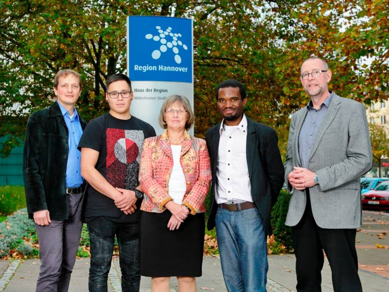 Eine Frau und vier Männer stehen vor dem Regionshaus in Hannover.