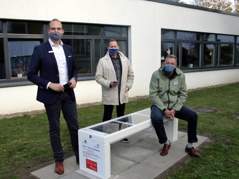 Zwei Männer stehen um eine Sitzbank mit Solarzellen und USB-Anschluss, ein Mann sitzt auf der Bank.