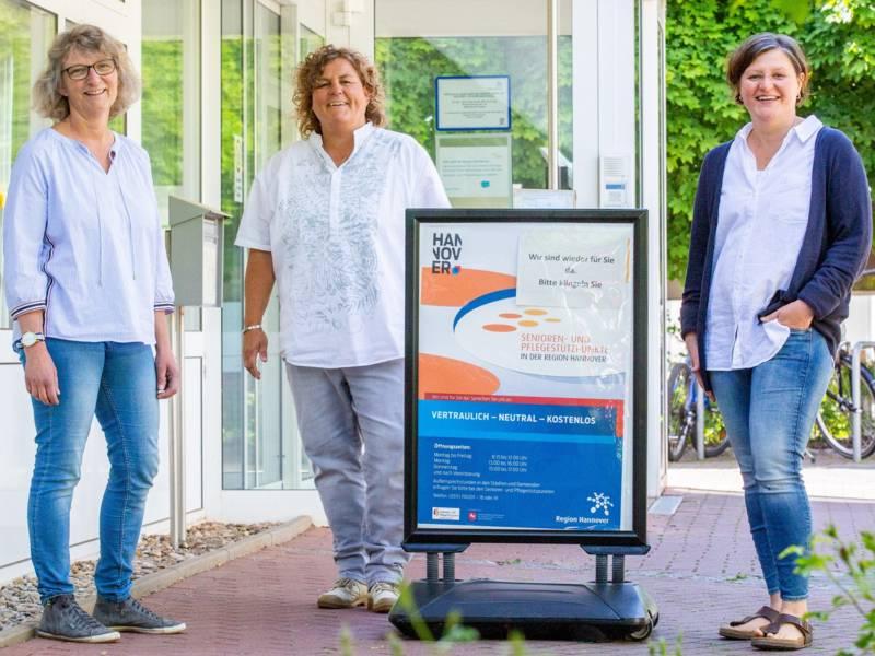 Drei Frauen stehen neben einem Aufsteller vor einer Eingangstür.