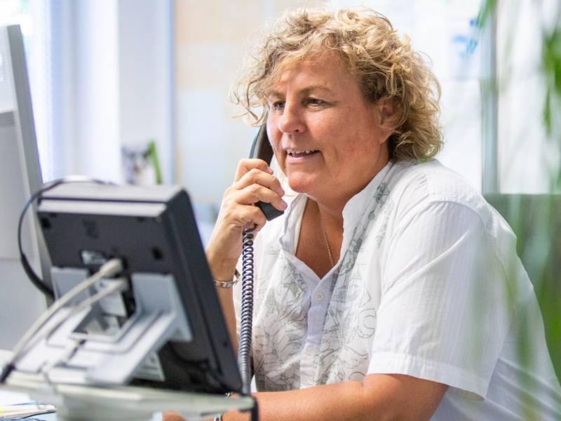 Eine Frau sitzt an einem Schreibtisch und telefoniert.