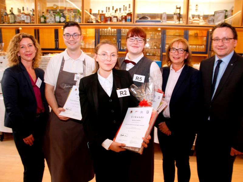 Vier Frauen und zwei Männer stehen nebeneinander, die Personen in der Mitte halten Urkunden. Im Hintergrund ist eine Bar mit Spitituosenflaschen zu erkennen.