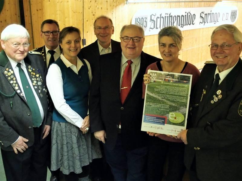 Sieben Personen stehen für ein Foto beisammen. Eine Frau und ein Mann halten eine Auszeichnung.