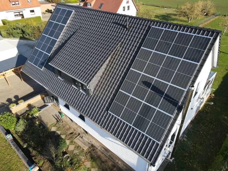 Luftaufnahme von einem Hausdach, auf dem eine Photovoltaik-Anlage zu sehen ist