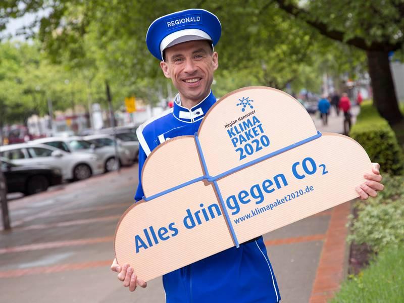 Mann in einer blauen Uniform, der ein Schild in Form einer Wolke trägt, auf dem steht: Alles drin gegen CO2