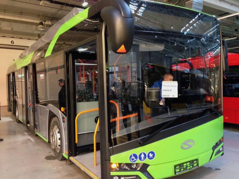 Ein Elektrobus, lackiert in den Farben Grün und Silbergrau, steht in einer Halle.