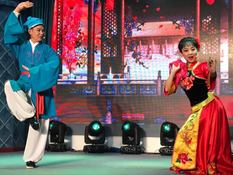 Ein Mann und eine Frau stehen in farbenfrohen Gewändern auf einer Bühne und tragen etwas vor.