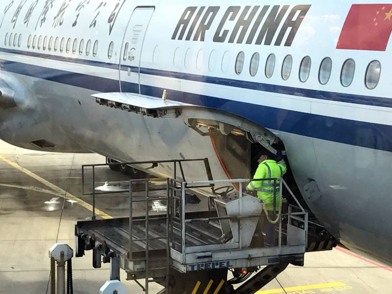 """Ein Arbeiter steht auf einer mobilen Hebebühne an der geöffneten Frachtraumluke eines Verkehrsfluigzeugs. Auf dem Flugzeug sind chinesische Schriftzeichen und die Buchstaben """"AIR CHINA""""."""