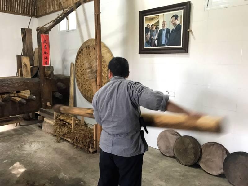 Ein Mann schlägt einen Pfosten auf eine Apparatur, um Sesamöl zu pressen.