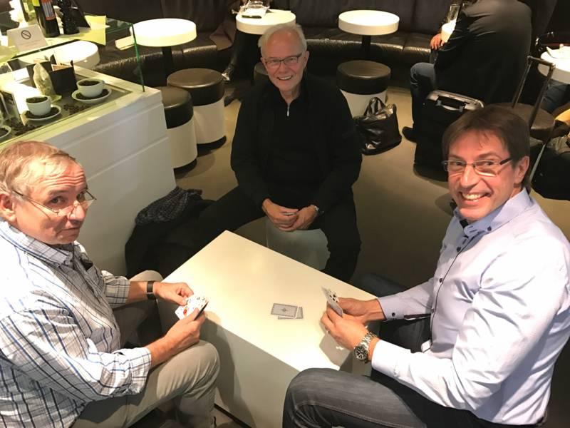 Drei Männer sitzen an einem Tisch und spielen ein Kartenspiel.