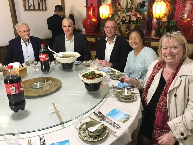 Drei Männer und zwei Frauen sitzen an einem runden Tisch, auf der Drehscheibe aus Glas in der Tischmitte stehen Getränke und Schüsseln mit Suppe.