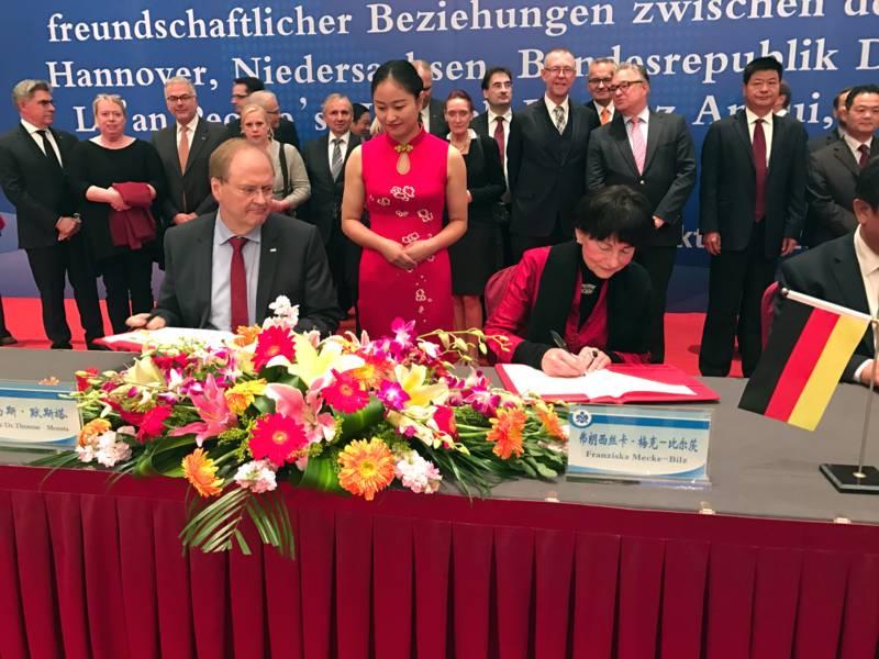 Ein Mann und eine Frau sitzen an einem Tisch und unterschreiben ein Dokument.