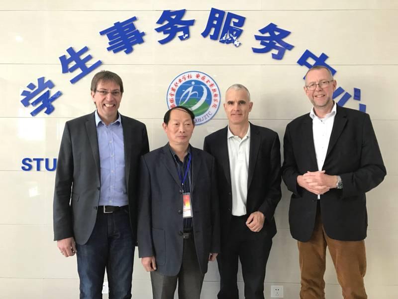 Vier Männer stehen vor dem Schriftzug einer Schule.