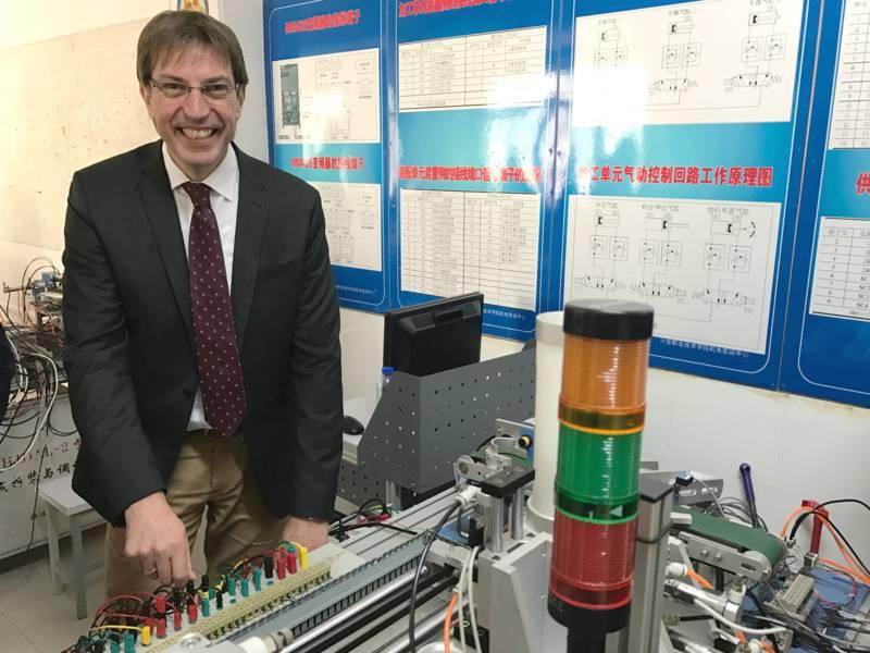 Ein Mann steht hinter einem Pult mit vielen Schaltern und Kabeln.