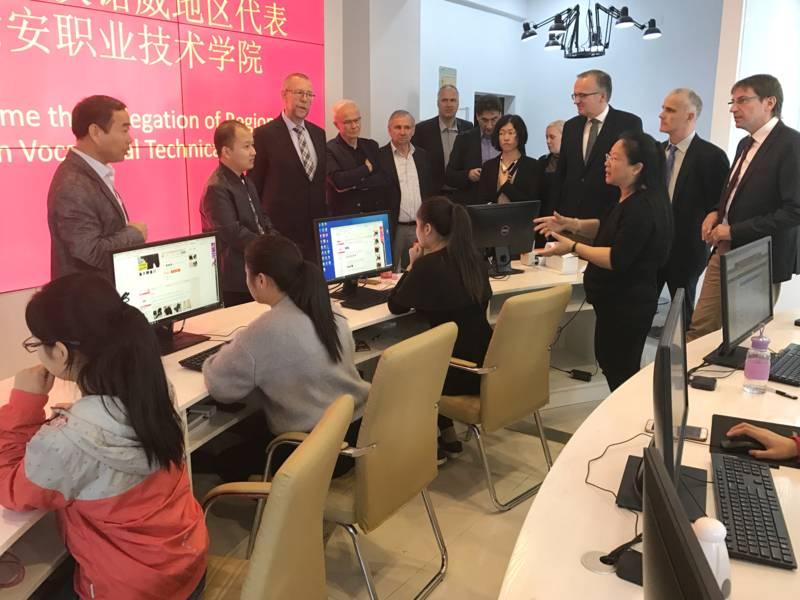 Schülerinnen sitzen an Computerbildschirmen, Teilnehmende der Delegation schauen ihnen beim Arbeiten am PC zu.