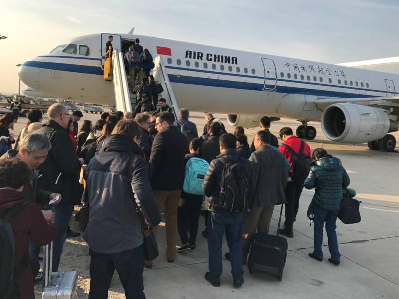 Menschen steigen über eine Außentreppe in ein Flugzeug.