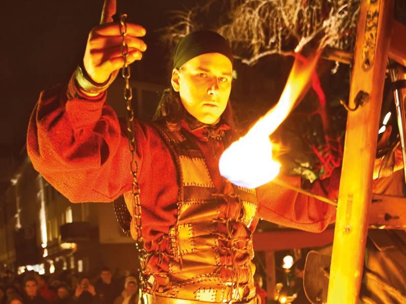 Ein Feuerkünstler in historischer Kleidung bei seiner Darbietung im historischen Dorf auf dem Weihnachtsmarkt Hannover