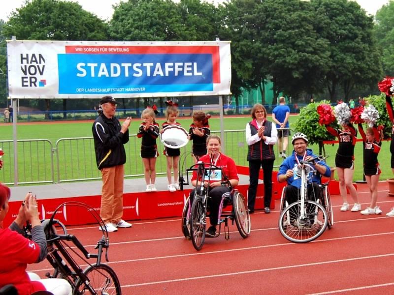 Hand-Biker, Kinder und Erwachsene auf einem Sportplatz.