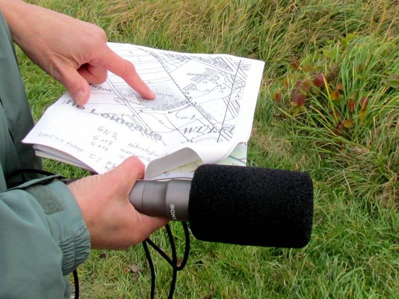 Eine Person hält ein Mikro und eine Karte in den Händen, im Hintergrund ist hohes Gras zu sehen