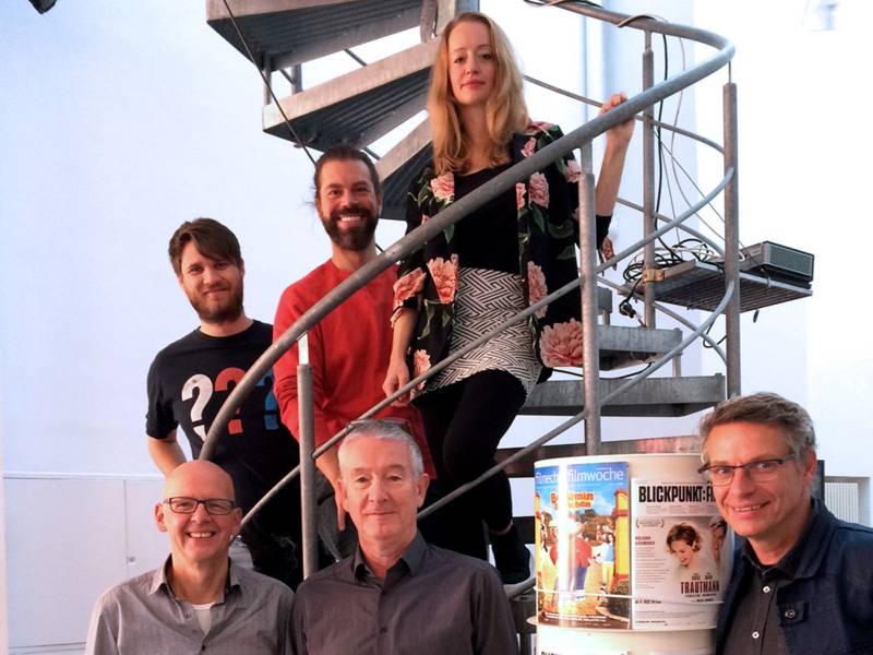 Sechs Personen posieren auf und vor einer Wendeltreppe, im Vordergrund rechts eine Säule mit Filmplakaten.