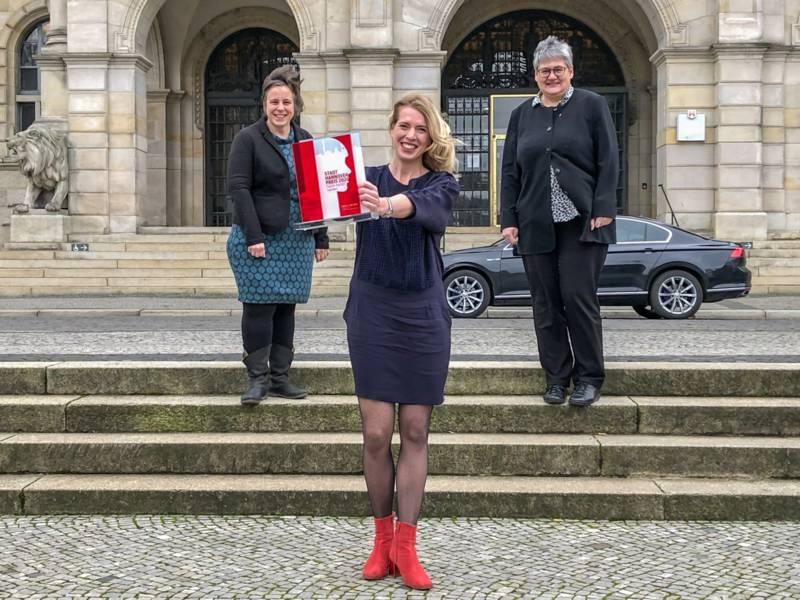 Drei Frauen stehen mit Abstand auf einer Treppe, im Hintergrund das Neue Rathaus