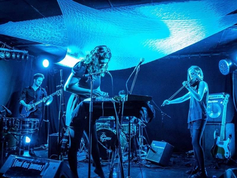 Links im Hintergrund ein Gitarrist, in der Mitte eine Musikerin am Keyboard, rechts im Hintergrund eine Geigerin auf einer in blaues Licht getauchten Bühne