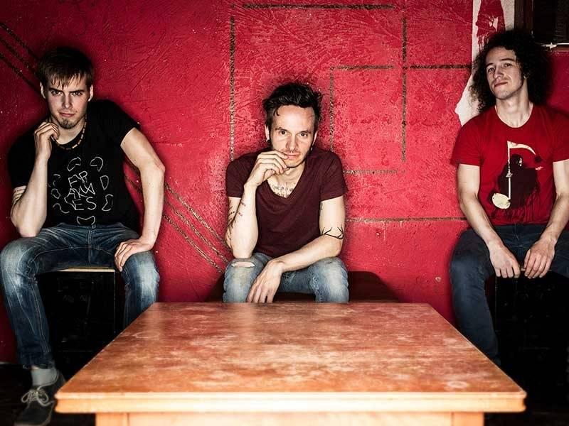 Drei Musiker vor einer rot gestrichenen Wand